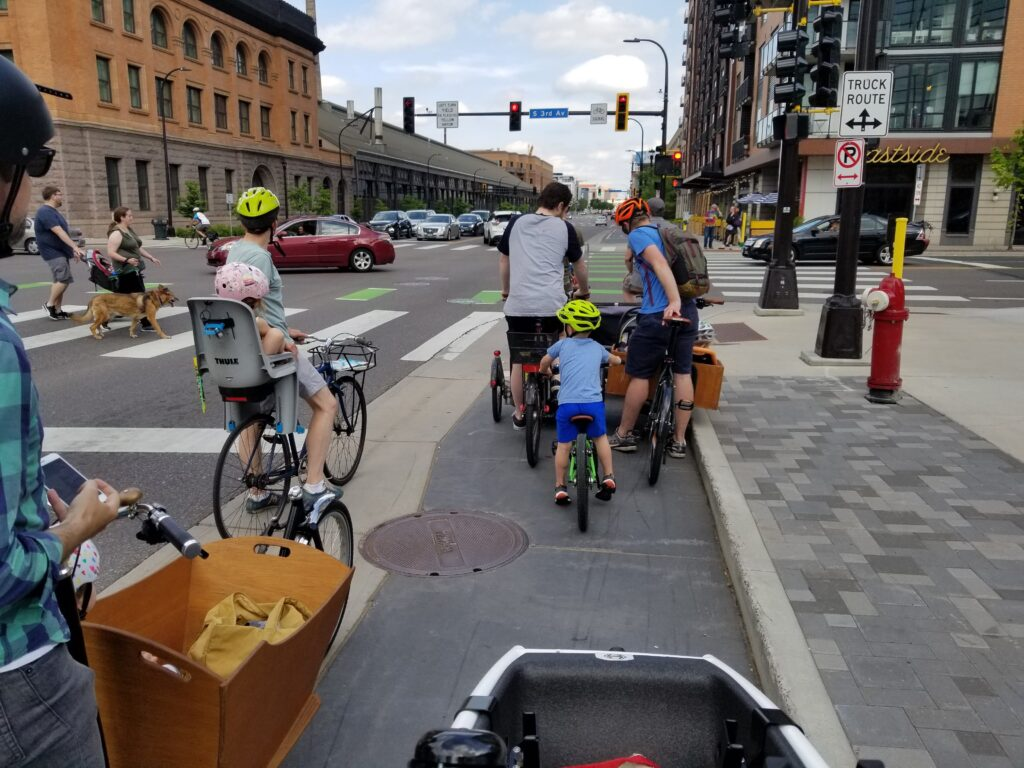 Families with kids biking in an urban environment. Cargo bikes, kids in bike seats, and little kid biking on own with parents in bike path or cycletrack. Dedicated space for biking community members.