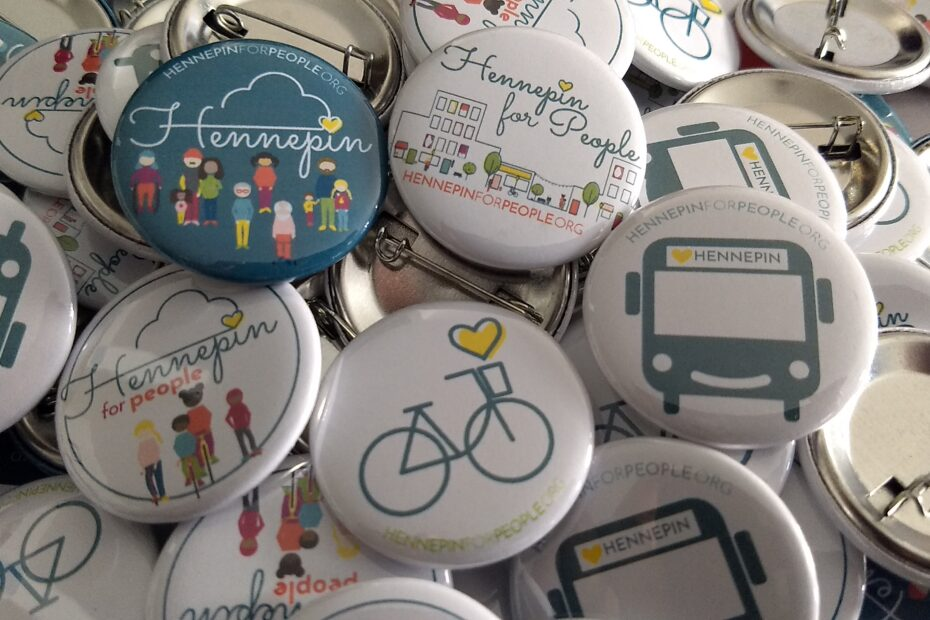 Bike with heart button. Kids on wheels buttons. Hennepin for People streetscape. Smiley face bus with yellow heart and Hennepin as route sign. Hennepin for People graphics of peoople.
