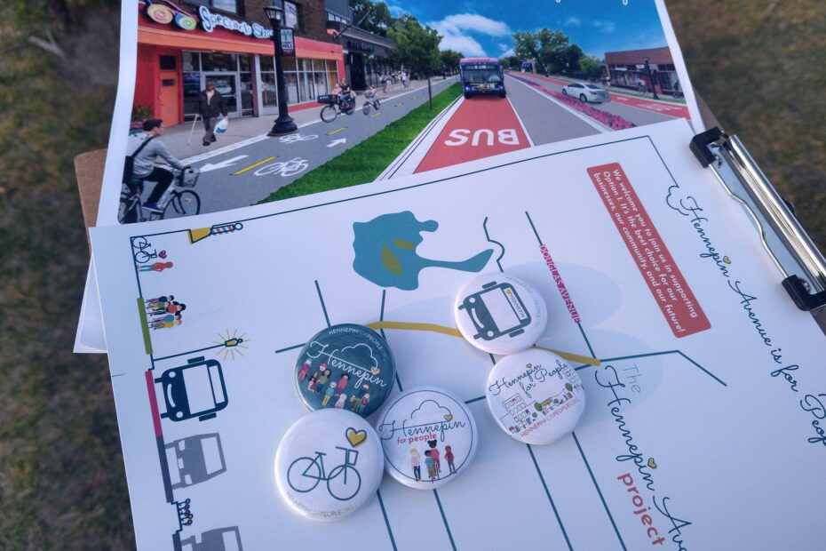 Clipboard with Hennepin for People outreach materials. Image of future street, map of project area, and buttons. Smiley bus face, Streetscape, Kids on wheels (biking, skateboarding, scooter), bike with yellow heart above, and our logo our people involved with Hennepin for People.