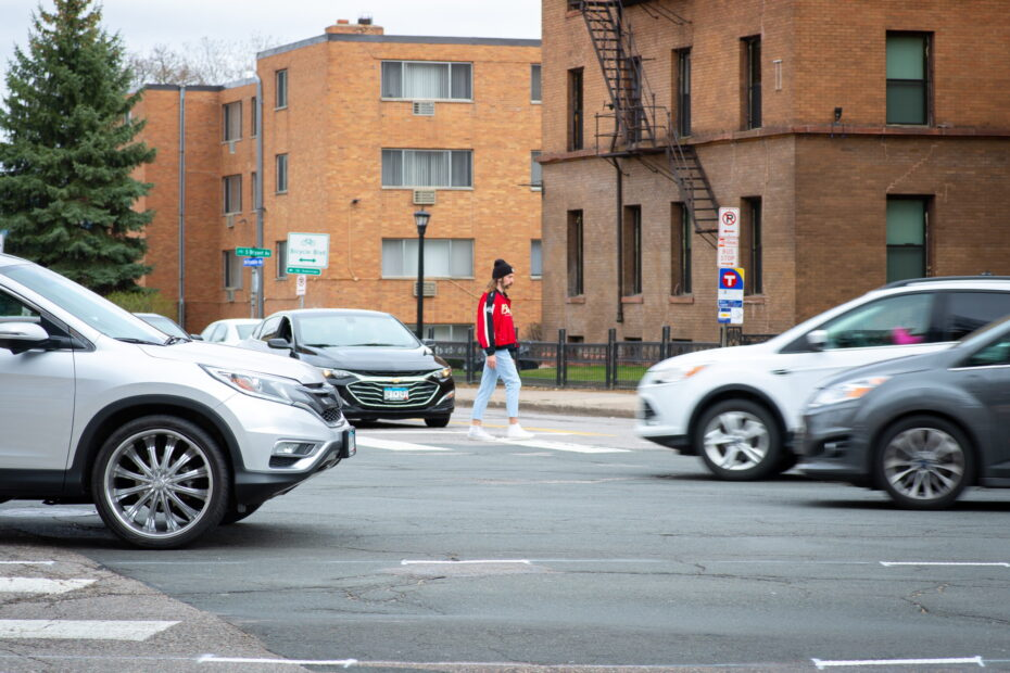 Man walking across street surrounded by cars.