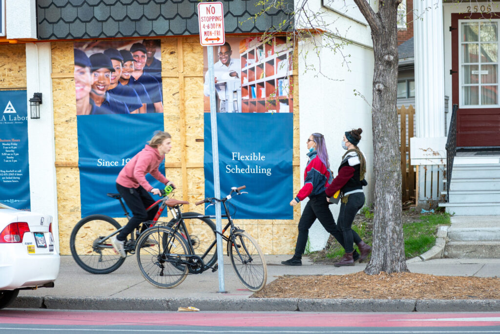Young teenager biking on sidewalk northbound. Two women are walking southbound on sidewalk.