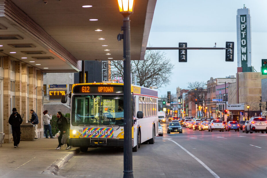 612 bus at Uptown Transit Station. Transit riders waiting at station. Uptown sign in background.