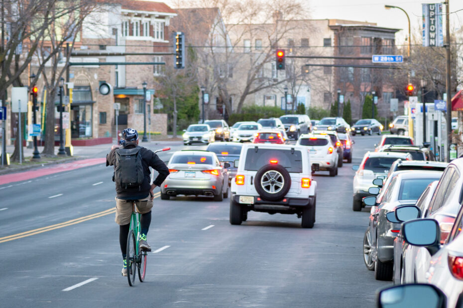 person biking with cars on Hennepin