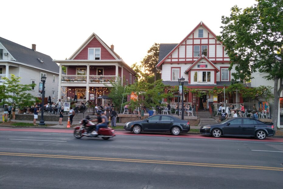 Street perspective of businesses. People dining outside with motorcycle riding by.