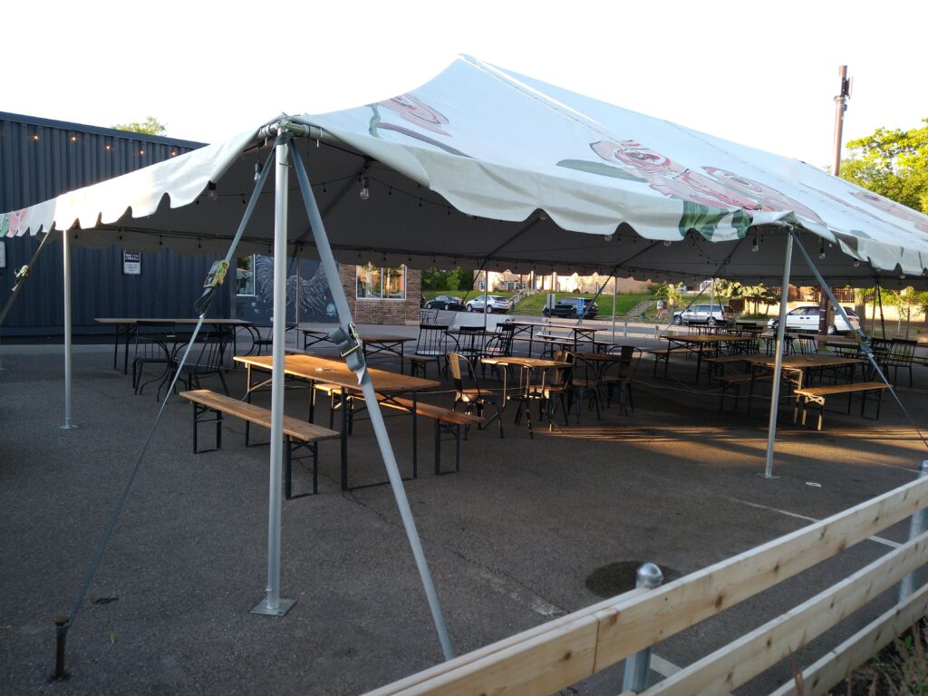 Custom large white tent covered in hand painted pink roses set up in parking lot. Lynhall on Lyndale converted parking lot to outdoor dining space.