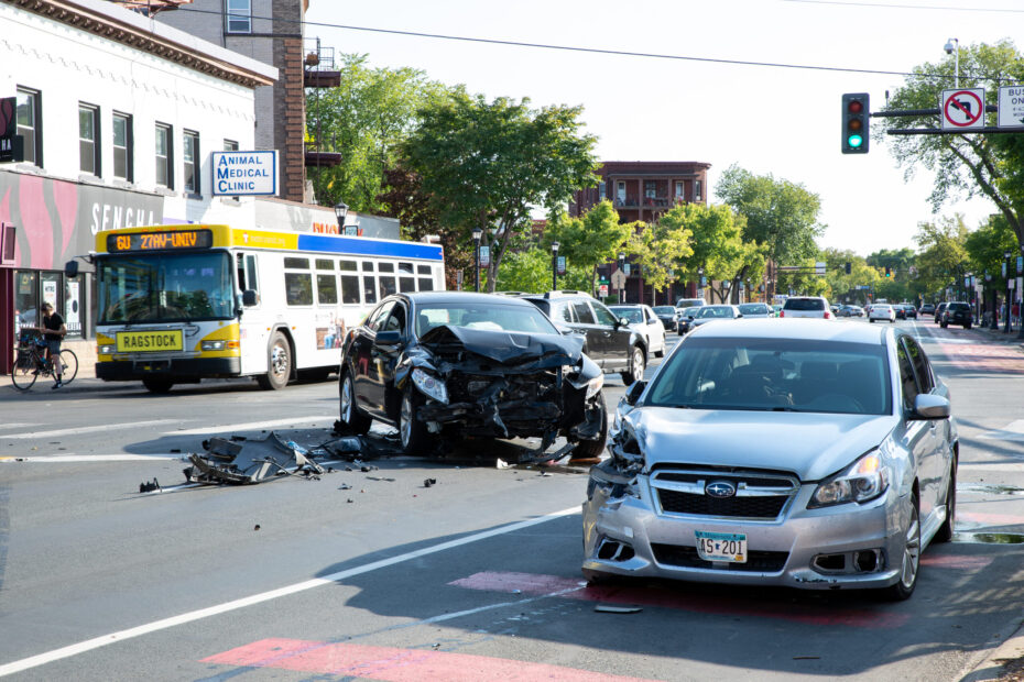 Two cars crashed and damaged. Red light runner. Bus in background. Biker on sidewalk observing. Car traffic in background.