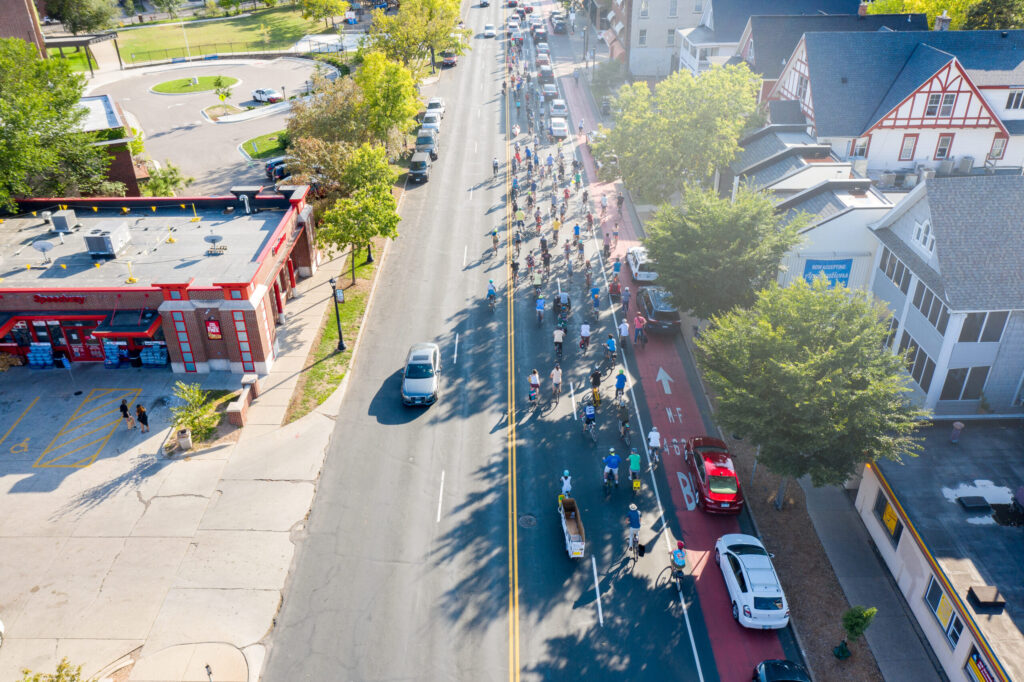 A hundred people on bikes on Hennepin Avenue. Bus lane filled with parked cars.